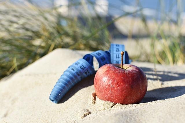 jablko v písku a stočený modrý metr